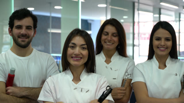 vídeos de stock e filmes b-roll de proud team of hairdressers at a salon all looking at camera smiling with arms crossed - spa treatment