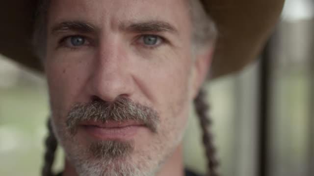 vídeos y material grabado en eventos de stock de proud texas man with cowboy hat and braided hair stares into camera - mirar fijamente
