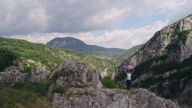 vídeos y material grabado en eventos de stock de mujer orgullosa agitando con bandera americana en las montañas - patriotismo