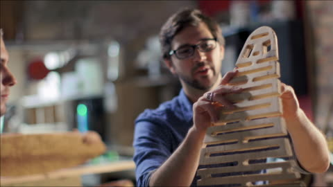 proud woodworker demonstrates flexibility of new frame design to student - verbesserung stock-videos und b-roll-filmmaterial
