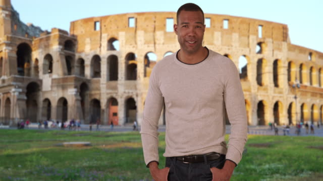 Proud youthful black male near Colosseum in Rome poses boldly