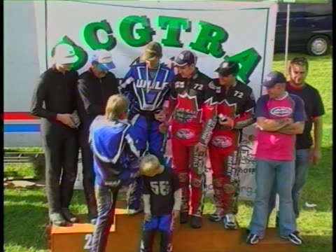 proudly receiving their trophies for a motorcross race the medal winners fall off the platform - ausrutscher stock-videos und b-roll-filmmaterial