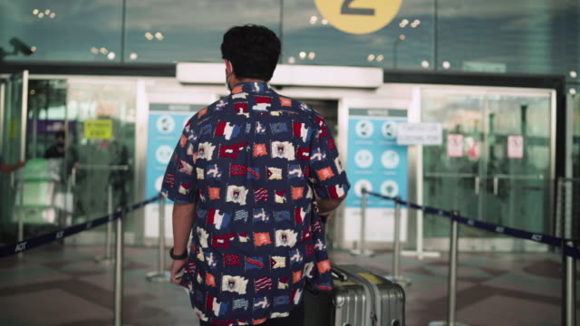 psengers men with a gray suitcase, go to the check-in counter airline airport - transportation building type of building stock videos & royalty-free footage