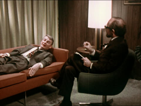 1969 psychiatrist taking notes while patient lying on couch talks - mental health stock videos & royalty-free footage