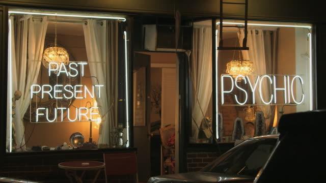 ms night psychic storefront with neon lights and crystal ball in window - taxi cab passes  / new york, new york, usa - spår bildbanksvideor och videomaterial från bakom kulisserna