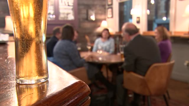 Pub general views ENGLAND London Wimbledon INT General views of reporter sitting with people drinking in pub / pint of beer / lager on bar Group in...