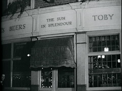 Pub 'The Sun In Splender' w/ unidentified male walking by ZI Window w/ Charrington's sign over glass LA INT British pub w/ two males standing talking...
