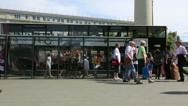 A BVG public bus drives away from bus stop in Berlin Germany on Wednesday May 21 Pedestrians walk past as a double decker bus pulls into a bus stop...