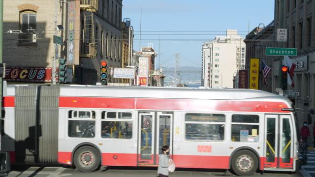 vidéos et rushes de public bus in san francisco chinatown amid the global coronavirus pandemic. - traverser