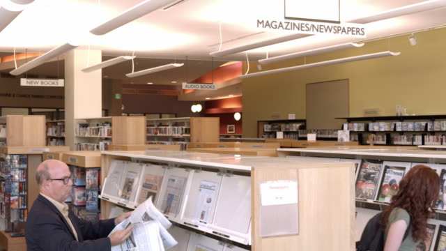 ws pan public library reading room for newspapers magazines and music cds with patrons browsing shelves for casual reading / rancho mirage, california, usa - rancho mirage stock videos & royalty-free footage