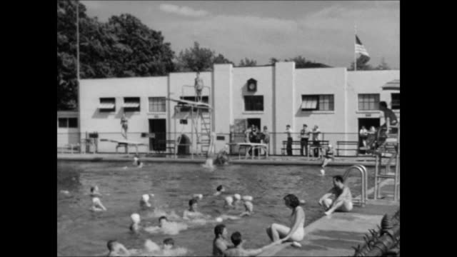 public pool w/ two diving boards & a high dive, people swimming, divers diving, father teaching daughter to swim, male life guard sitting in tall... - bathhouse stock videos & royalty-free footage