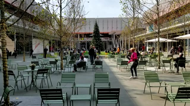 public seating area, with green, metal tables and chairs, small trees strung with lights, and a lit christmas tree at one end, surrounded by a... - balding stock videos & royalty-free footage