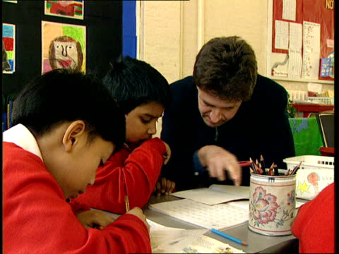 london islington winton primary school int gv children in uniform sitting working in classroom cms two boys writing cms teacher at desk with two boys... - school uniform stock videos and b-roll footage
