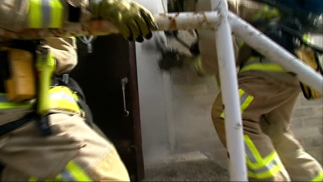 preparations bedfordshire luton ext firefighters using hose and entering smoking building during training exercise jamie newell interview sot - 向かう点の映像素材/bロール