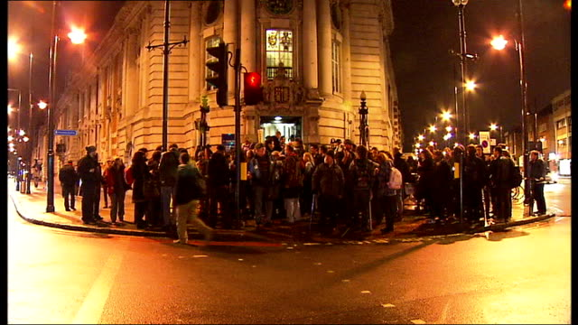 vídeos de stock e filmes b-roll de council budgets protesters invade lambeth council chamber ext / night back view of demonstrators gathered outside lambeth town hall building trying... - town hall