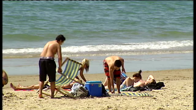 vídeos y material grabado en eventos de stock de fears felt by local council leaders dorset bournemouth reporter to camera young people playing beach volleyball people setting out deckchairs by the... - bournemouth