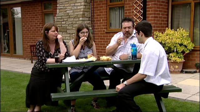 legal aid faces cut of 350 million pounds; england: lincolnshire: ext green family at outdoor table in garden rick green feeding son andrew green... - 画面切り替え カットアウェイ点の映像素材/bロール