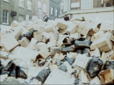 public workers' dispute: dustmen's strike:; a) boing england: london: berwick street market: ext pan huge pile of rubbish at kerbside 6/2/79/nat - dustman stock videos & royalty-free footage