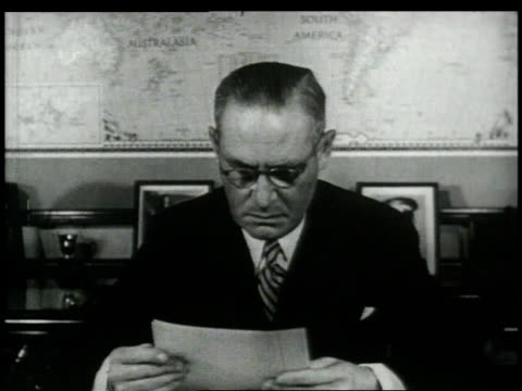 vidéos et rushes de publisher arthur hays sulzberger sitting at his desk reading paper, man coming in to show him something / new york city, new york, united states - editorial