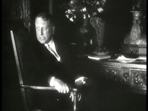 vidéos et rushes de publisher william randolph hearst seated in chair at ornate desk turning speaking to someone off-camera. hearst's san simeon ranch. - editorial