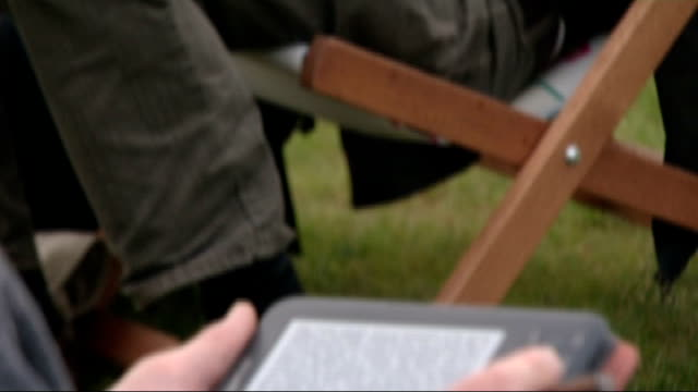 sales of hardback books in decline as ebooks take over; tx 17.8.2011 scotland: edinburgh: ext shots of man in deckchair reading paperback book and... - libro in brossura video stock e b–roll