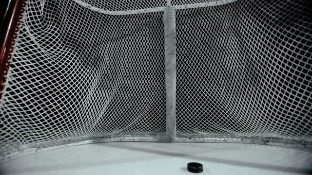 vídeos de stock e filmes b-roll de slo mo ds puck sliding into the goal on a hockey rink - pista de patinagem no gelo
