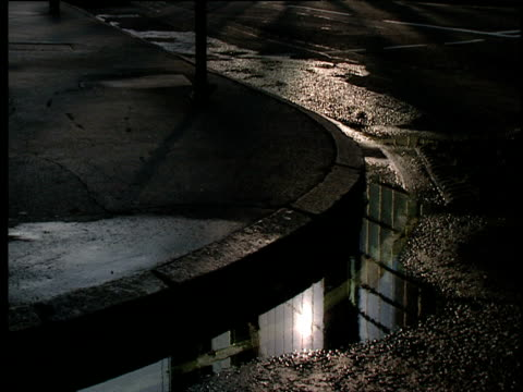 Puddle in gutter with sun and building reflected