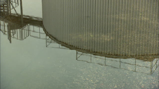 cu puddle of water on road reflecting storage tank / vaxjo, sweden - vaxjo stock videos & royalty-free footage