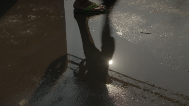 A puddle reflects the shadow of a walking man, Mumbai, Maharashtra, India.