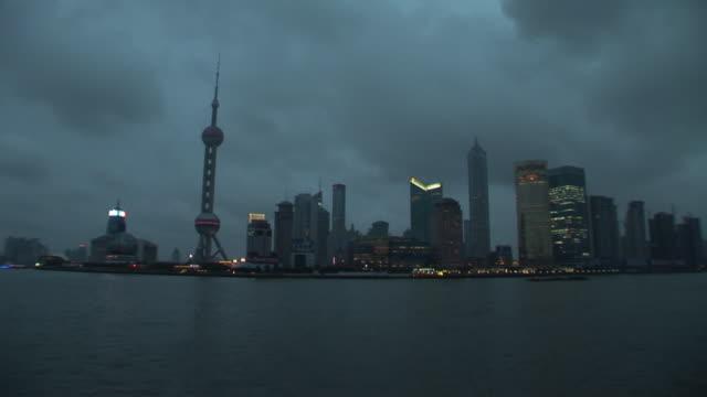 ws, pudong skyline illuminated at dusk across huangpu river, shanghai, china - river huangpu stock videos & royalty-free footage
