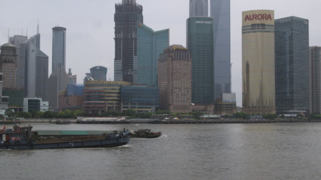 WS Pudong skyscrapers with barges on Huangpu River in foreground / Shanghai, China