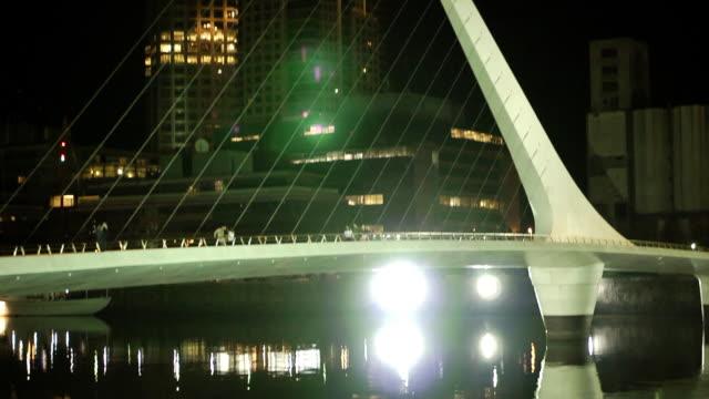 puente de la mujer footbridge lights bridge reflecting in water skyscrapers bg - puente de la mujer stock videos & royalty-free footage
