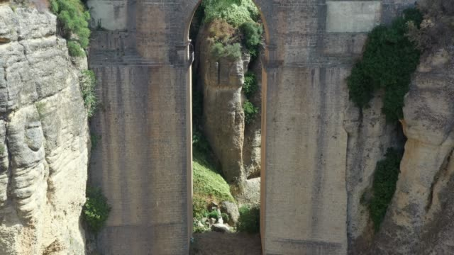 puente nuevo between the canyon and nearby village / ronda, spain - puente stock videos & royalty-free footage