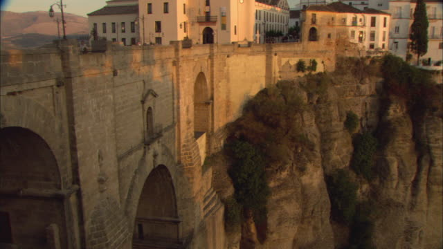 stockvideo's en b-roll-footage met ws pan puente nuevo leading into town and buildings on top of cliff at sunset / ronda, andalusia, spain - puente