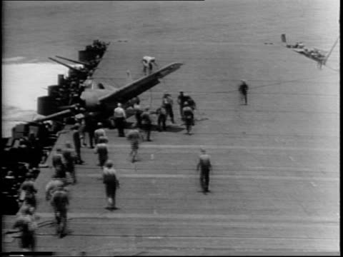 puffs of smoke in distance as seen from deck of ship distant view of battle and gun firing / plane on deck that has slid to edge / soldiers rush to... - battle stock videos & royalty-free footage
