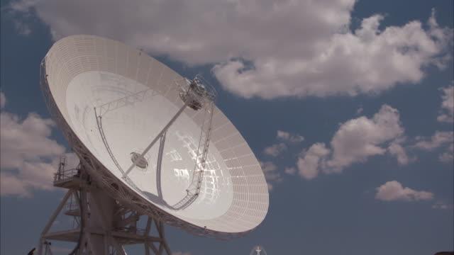 vídeos y material grabado en eventos de stock de puffy clouds drift over a satellite dish. - antena parabólica