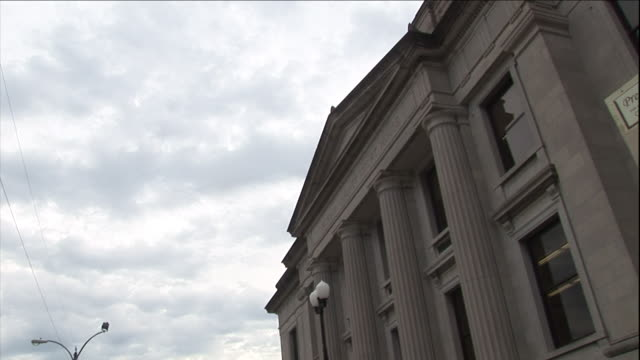 puffy clouds hang in the sky over a courthouse. - palazzo di giustizia video stock e b–roll