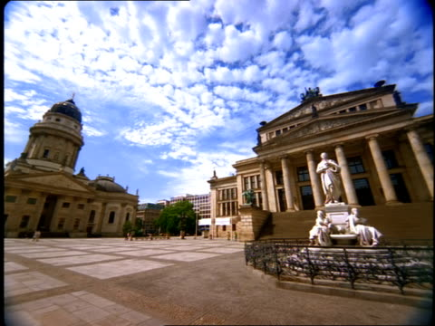 Puffy clouds hang in the sky over Gendarmenmarkt town square in Berlin, Germany.