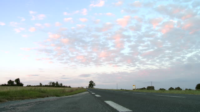 ws puffy pink clouds over country road in city with truck driving by / beaune, burgundy, france - 長い点の映像素材/bロール