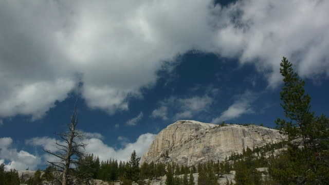 tl puffy white clouds moving over granite mountain peak in wilderness, yosemite national park, california - granite stock videos & royalty-free footage