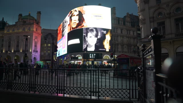 pull back as traffic and pedestrians pass in front of the bright lights of piccadilly circus, london - 商業看板点の映像素材/bロール