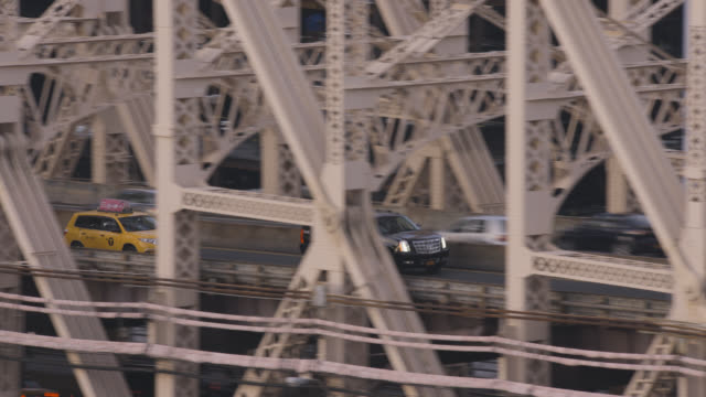 pull back from black suv driving across queensboro bridge. east river and city skyline partially visbile. smoke stacks visbile across from bridge.