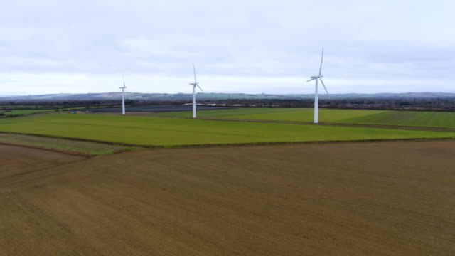 pull back from three wind turbines spinning - power station stock videos & royalty-free footage