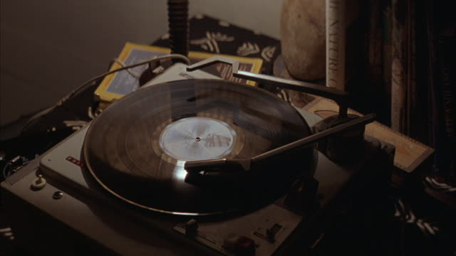 vidéos et rushes de pull back of record player with record turning on small table with lamp and books to see wooden chest sitting on floor with artifacts on top. see lamp on table lit and table cloth. - platine de disque vinyle