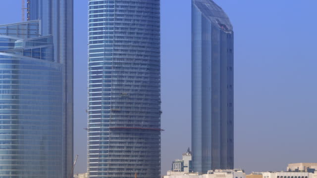 Pull back rom skyscrapers to reveal Abu Dhabi skyline with couple in foreground