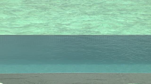 vídeos de stock, filmes e b-roll de pull back shot beach pool male maldives - lago infinito