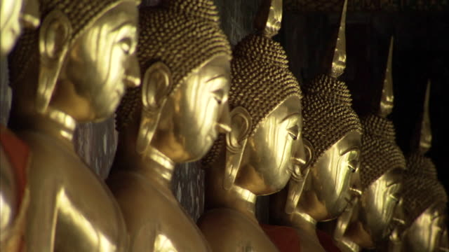 vídeos de stock e filmes b-roll de pull focus across a row of golden buddha statues in a temple. - buda