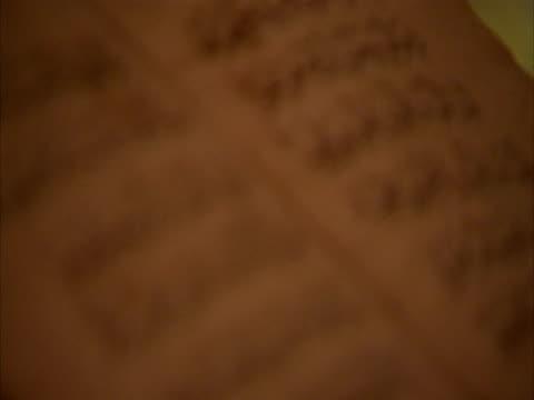 pull focus across old arabic script, syria (sound available) - arabic script stock-videos und b-roll-filmmaterial