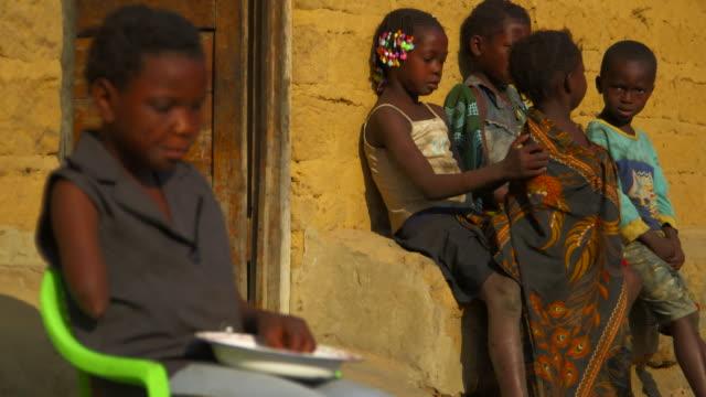 pull focus angolan landmine victim eats fruit outside - victim stock videos & royalty-free footage