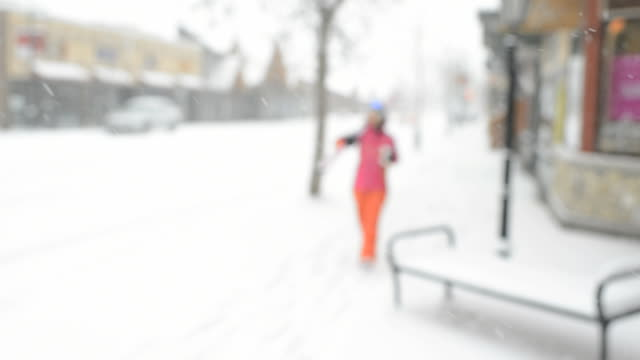 Pull focus as woman carries skis along village street